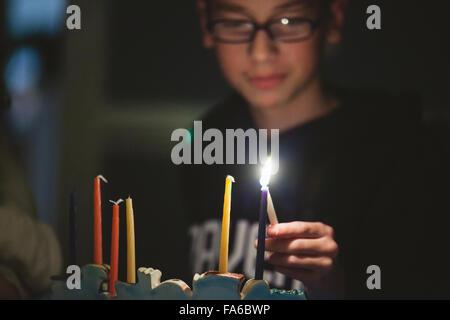 Teenage boy lighting Menorah during Hanukkah - Stock Photo