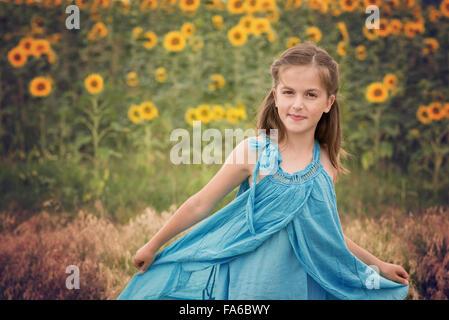 Girls in a sunflower field spinning around - Stock Photo