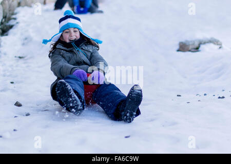 Girl on a sledge sliding down a hill in the snow - Stock Photo