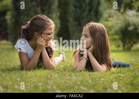 Two girls talking and smiling - Stock Photo