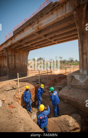 Workers construct a bridge along the Nampula to Rio Ligonha Road in Northern Mozambique, SE Africa. - Stock Photo