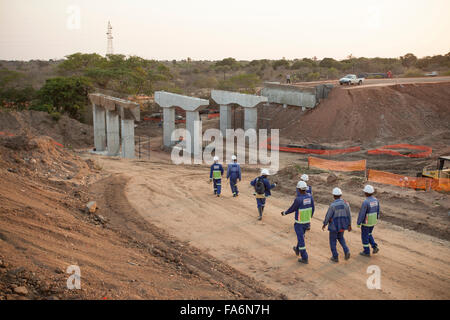 Workers construct a new highway overpass in Nampula Province, Mozambique, SE Africa. - Stock Photo