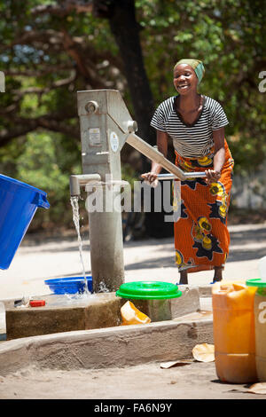 Community members draw clean water from a borehole in Mecupes village, Northern Mozambique. - Stock Photo