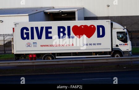 NHS 'Give Blood' Transfusion mobile unit lorry travelling along the Kingsway West Dual Carriageway in Dundee, UK - Stock Photo