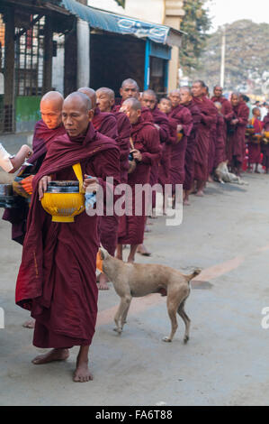 Buddhist monk in a long queue in Shwe Kyet Yet village in Mandalay Region, Myanmar, receiving food into his alms - Stock Photo