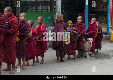 Group of juvenile Buddhist monks on alms round queuing up for food alms in Shwe Kyet Yet village, Mandalay Region, - Stock Photo