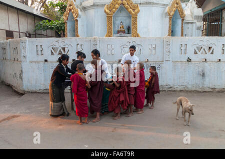 Group of juvenile Buddhist monks receiving food alms on alms round in Shwe Kyet Yet village in Mandalay Region, - Stock Photo