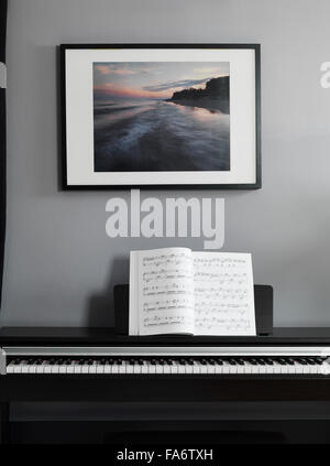 Digital piano keyboard with music scores in a room interior - Stock Photo