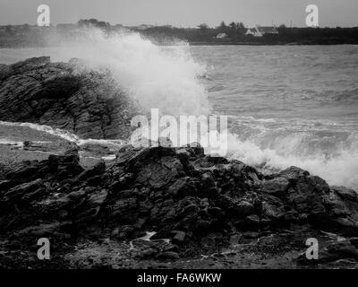 Black and white image of waves crashing over the rocks at Rhoscolyn beach - Stock Photo