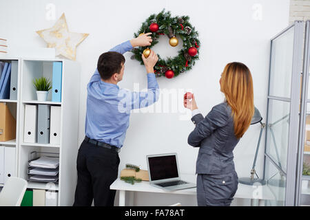 Businessman decorating coniferous Christmas wreath with his colleague near by - Stock Photo