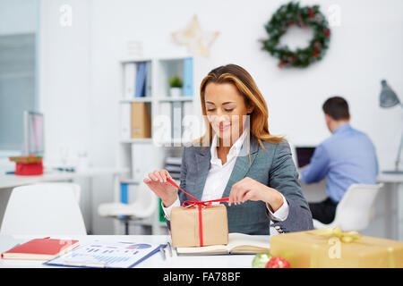 Young businesswoman unpacking gift-box in office - Stock Photo