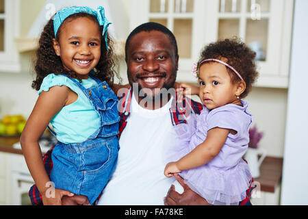 Happy African-American father and two cute girls looking at camera - Stock Photo