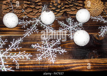 White balls with snowflakes and pine cones on a dark board - Stock Photo