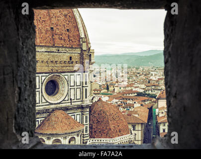 View of the Duomo Cathedral and Great synagogue in Florence through the stone window, Florence, Tiscany, Italy. - Stock Photo