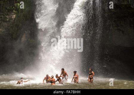 tourists enjoying a bath in the Tegenungan waterfall near Ubud, Bali, Indonesia - Stock Photo