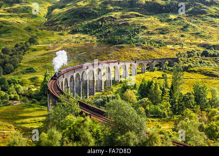 Glenfinnan Railway Viaduct in Scotland with the Jacobite steam train passing over - Stock Photo