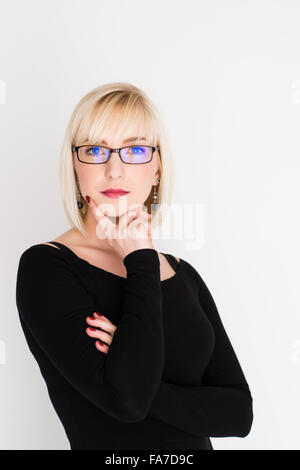 A young slim blonde blond haired woman girl, intellectual, clever, intelligent, thinking, pondering, thoughtful, - Stock Photo
