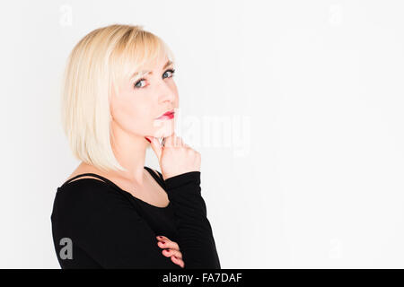 Decision making - difficult life choices and options : A young slim blonde blond haired woman girl, thinking, pondering, - Stock Photo