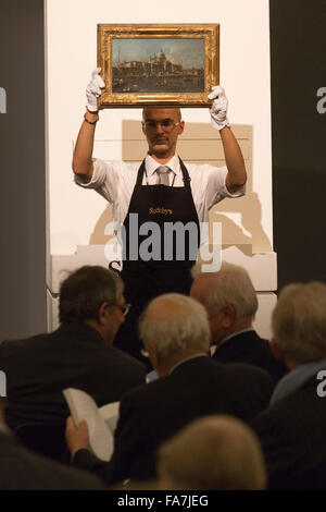 Handler presenting a painting. The auction for paintings from the Old Master & British Paintings Evening Sale takes - Stock Photo