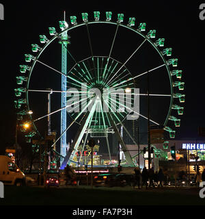 The big wheel at the Alexanderplatz Christmas market in Berlin, Germany. The television tower overlooks the Ferris - Stock Photo