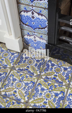 Detail of the tiled hearth and fireplace in the Sewing Room at Nuffield Place, Oxfordshire. The house was designed - Stock Photo