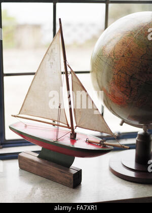 A vintage model boat and a globe, displayed on a windowsill in Portland House, Dorset. The house was built in 1935 - Stock Photo