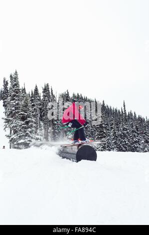 Side view of skier grinding on tube shaped obstacle, Whistler terrain park, British Columbia, Canada - Stock Photo