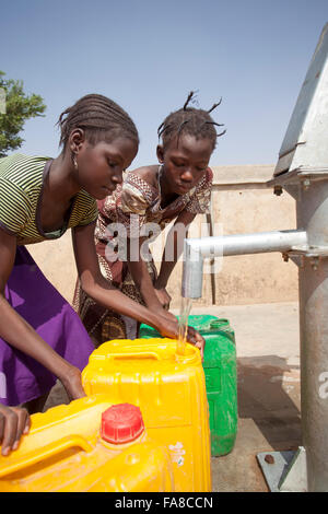 Girls get fresh water from a well in Kouka Department, Burkina Faso, W. Africa. - Stock Photo