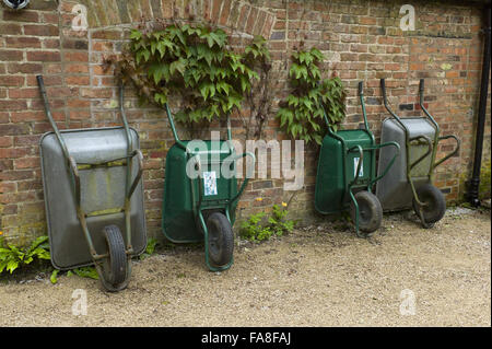 Wheelbarrows leaning against the garden wall outside the gardener's hut at Hare Hill, Cheshire. - Stock Photo