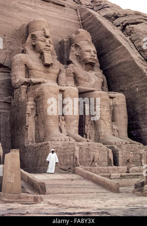 An Egyptian antiquities guard stands in front of two of the four colossal statues of Pharaoh Ramses II that dominate - Stock Photo