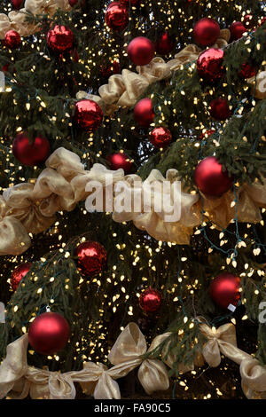Red balls with golden ribbons and lights on a giant outdoor Christmas tree Toronto - Stock Photo