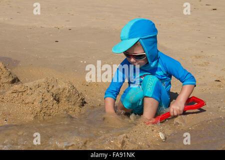 Boy playing on the beach at Praia De Santa Eulalia, near Albufeira, Algarve, Portugal - Stock Photo