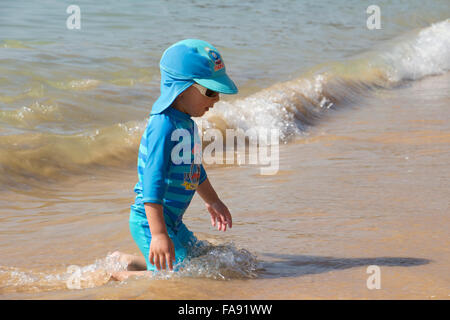 Boy playing on the beach at Praia De Santa Eulalia, near Albufeira, Algarve, Portugal - Stock Photo