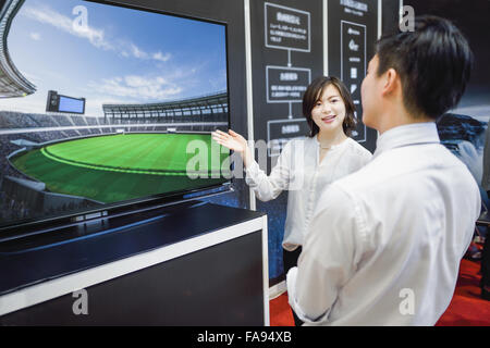 Young attractive Japanese businesswoman entertaining customer at fair booth - Stock Photo