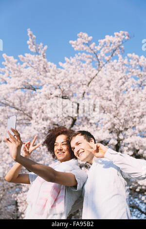 Multi-ethnic tourist couple enjoying cherry blossoms in Japan - Stock Photo