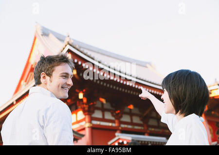 Young multi-ethnic couple enjoying tourism in Tokyo - Stock Photo