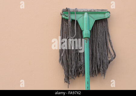 Old mop lying against a pink wall. - Stock Photo