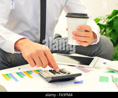 closeup of a young caucasian businessman using a calculator on a table full of charts and a cup of coffee in his - Stock Photo