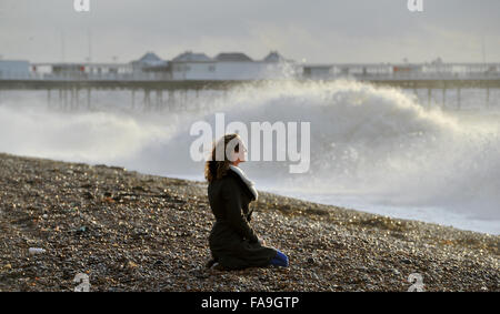 Brighton Sussex UK 24th December 2015 - A young woman watches the waves crash in on Brighton beach as Storm Eva - Stock Photo