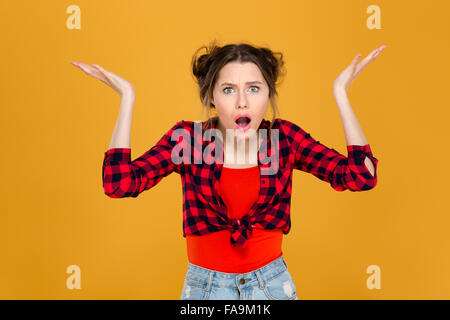 Shocked confused young woman with opened mouth and raised hands holding copyspace on both palms over yellow background - Stock Photo