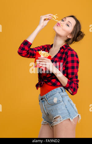 Amusing comical cute young woman in plaid shirt and jeans shorts having fun with french fries over yellow background - Stock Photo
