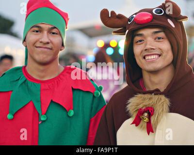 U.S. Air Force Airman 1st Class Barry Fernandez and Senior Airman Cuong Pham dress as an elf and reindeer during - Stock Photo