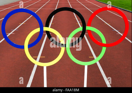 RIO DE JANEIRO, BRAZIL - FEBRUARY 12, 2015: Olympic rings stand in front of the lanes of a red running track. - Stock Photo