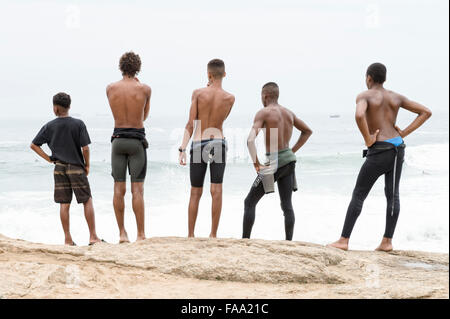 RIO DE JANEIRO, BRAZIL - OCTOBER 22, 2015: Brazilian surfers in wetsuits stand looking at incoming waves at Arpoador. - Stock Photo