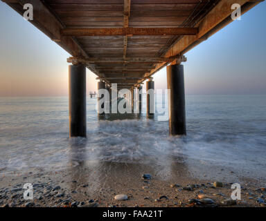 Rusty metallic  pier from sea level in horizontal composition creating a diagonal tunnel. - Stock Photo