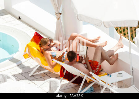 Young tanned Caucasian couple in bikini and shorts sitting on sun loungers on patio under parasol, in the sunshine - Stock Photo