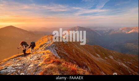 Tourists on the trail, autumn colors in Tatra Mountains, Poland - Stock Photo
