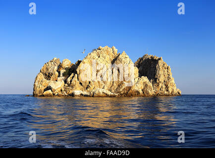 Small rocky island protruding from the surface of the sea - Stock Photo