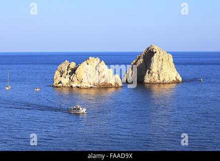 Two small rocky islands protruding from the surface of the sea - Stock Photo