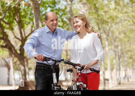 Elderly happy couple on summer weekends walking with bicycles - Stock Photo